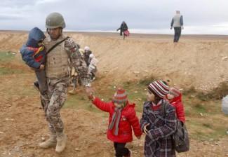Syrian refugees arrive at a Jordan border town