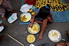 epa04789372 A young Homeless Indian eats free food on a street in Calcutta, India, 08 June 2015. According to local reports a Calcutta based NGO which serves free food has become popular among the homeless.  EPA/PIYAL ADHIKARY