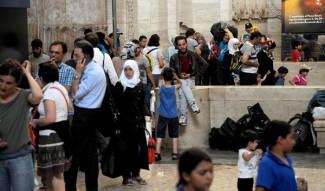 Decine di profughi siriani arrivati in treno da Taranto alla Stazione di Milano dove Comune e Protezione civile hanno allestito brandine e portato cibo e acqua, 10 Giugno 2014. ANSA/ DANIELE MASCOLO