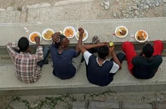 Alcuni migranti mangiano all'interno della tendopoli allestita alla stazione Tiburtina dalla Croce Rossa, Roma, 14 giugno 2015. ANSA/ALESSANDRO DI MEO