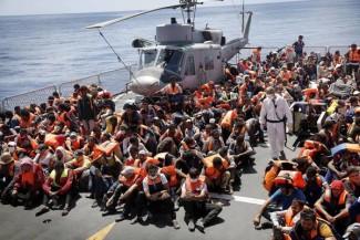 Profughi a bordo della Fregata Euro impegnata nell'operazione Mare Nostrum (sullo sfonfo la fregata Virgilio Fasan), Mar Mediterraneo Meridionale, 30 Agosto 2014. ANSA/GIUSEPPE LAMI