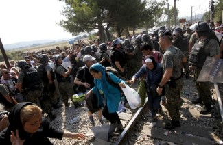 Macedonian police officers block a larger group of migrants from storming past the border,  first letting migrant families with children to enter into Macedonia from Greece, on the border line between the two countries, near southern Macedonia's town of Gevgelija, on Wednesday, Aug. 26, 2015. Thousands of migrants have poured into Macedonia and board trains and busses that are taking them a step closer to the European Union. (ANSA/AP Photo/Boris Grdanoski)
