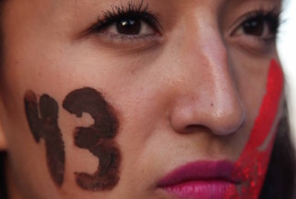 A female demonstrator with the number 43 painted on her face marches in protest for the disappearance of 43 students in the state of Guerrero, in Mexico City, Wednesday, Nov. 5, 2014. Federal police detained yesterday Iguala Mayor Jose Luis Abarca and his wife, Maria de los Angeles Pineda, who are accused of ordering the Sept. 26 attacks on teachers' college students that left six dead and 43 still missing. (AP Photo/Marco Ugarte)
