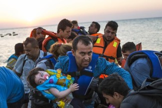 A man carries a girl in his arm as migrants arrive at a coast on a dinghy after crossing from Turkey in the southeastern island of Kos, Greece, during the sunrise early Thursday, Aug. 13, 2015. Greece has become the main gateway to Europe for tens of thousands of refugees and economic migrants, mainly Syrians fleeing war, as fighting in Libya has made the alternative route from north Africa to Italy increasingly dangerous. (ANSA/AP Photo/Alexander Zemlianichenko)