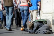 Un mendicante chiede l'elemosina sdraiato su un marciapiede in una strada di Roma oggi 19 ottobre 2011.   ANSA/ ETTORE FERRARI