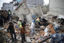 People and rescue workers survey damaged buildings looking for survivors, a day after a massive earthquake, in Kathmamdu, Nepal, 26 April 2015. More than 1,800 people were confirmed dead and many more were feared trapped under rubble Sunday in Nepal's worst earthquake in more than 80 years. The official death toll from the magnitude-7.9 earthquake reached 1,805, the Home Ministry said. One official said that figure could triple. Saturday's quake flattened buildings across the country and razed many historic landmarks. It was also felt in China, Bangladesh and India, where more than 40 deaths were reported. Buildings in the ancient centre of Kathmandu were destroyed, leaving mounds of timber and rubble, local television reported.  ANSA/NARENDRA SHRESTHA
