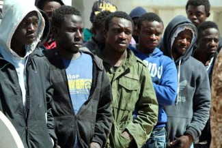 epa04161673 Some of the migrants, who were arrested after an attempt to reach Europe, wait before being transferred to police facilities in Tripoli, Libya, 10 April 2014. Naval coastguard said they had captured some 46 African migrants at sea after disembarking from the port of Tripoli.  EPA/SABRI ELMHEDWI