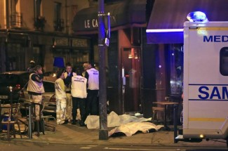 RETRANSMISSION FOR ALTERNATIVE CROP - Medics attend the scene as victims lay on the pavement outside a Paris restaurant, Friday, Nov. 13, 2015.  Police officials in France on Friday report multiple terror incidents, including shootings, explosions and hostage taking, leaving many dead. (ANSA/AP Photo/Thibault Camus)