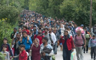 epa04930489 Migrants who had arrived from Roszke by train, walk toward Austria in Hegyeshalom, 168 kilometers west from Budapest, Hungary, 14 September 2015. Thousands of migrants were rushing to reach the EU-member state Hungary before a new law there effectively closes its borders on 15 September.  EPA/CSABA KRIZSAN HUNGARY OUT