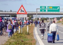 Migrants, mainly from Syria and Iraq, seen walking at the E45 freeway near Kliplev, Denmark, 09 September 2015. Thousands of the migrants arrived early morning at Padborg with a train from Germany and were placed at a school from where they fled, to try to get to Sweden by walking the freeway. The police closed the freeway for security reasons.  ANSA/BENJAMIN NOLTE