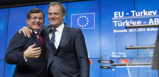 European Council President Donald Tusk, right, puts his arm on the shoulder of Turkish Prime Minister Ahmet Davutoglu after a media conference at an EU-Turkey summit in Brussels on Sunday, Nov. 29, 2015. At a high-profile summit in Brussels on Sunday, European Union leaders will look to offer Turkey 3 billion euros ($3.2 billion), an easing of visa restrictions and the fast-tracking of its EU membership process in return for tightening border security and take back some migrants who don't qualify for asylum. (AP Photo/Virginia Mayo)