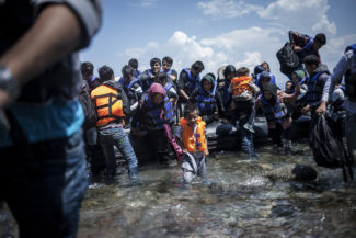 A young Afghan boy and other new arrivals transiting through Turkey, disembark from a boat in the Greek island of Lesvos.