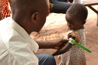 A Medecins Sans Frontieres (MSF) staff checks a child for malnutrition  during a measles vaccination campaign in Samba and neighboring zones in Maniema region, DRC.   26 MSF teams plan to vaccinate more than 58.000 children, in one week.